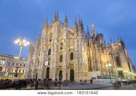 Milan Cathedral, Duomo di Milano. Famous gothic cathedral church of Milan, Italy, Europe. Black and white image shot at dusk from square full of people.