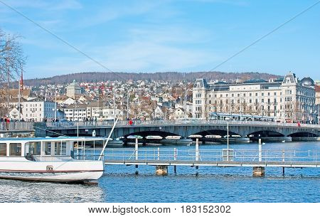 ZURICH SWITZERLAND - MARCH 20 2011: The walk along the Zurichsee (Zurich lake) with the view on the Quaibrucke bridge and the buildings of old town on March 20 in Zurich.