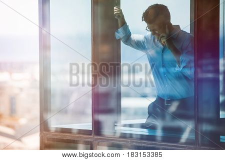 Smiling mature businessman standing inside office building and talking on cell phone. Male executive standing by glass window using mobile phone.