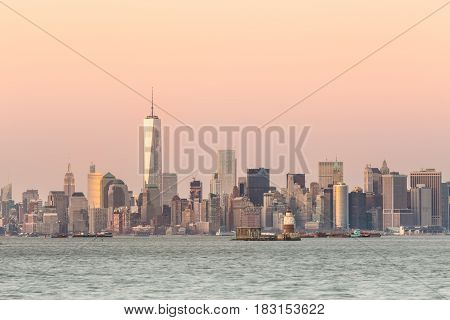 New York City Manhattan downtown skyline at dusk with skyscrapers illuminated over Hudson River panorama. Horizontal composition, copy space.