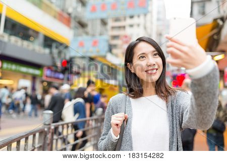 Woman taking selfie by cellphone in Hong Kong