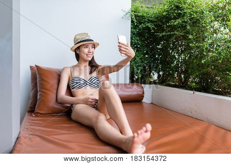 Woman taking selfie by mobile phone in resort