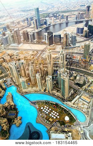 DUBAI UAE - JANUARY 28 2017:Top aerial view of a Dubai downtown in Dubai UAE at sunrise. Modern cityscape with skyscrapers Dubai fountain and artificial canal.