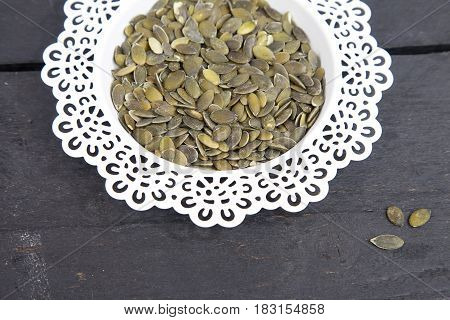 Pumpkin seed in white bowl on wooden background