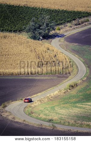 Winding road and car at Moravian Fields in Czechia.