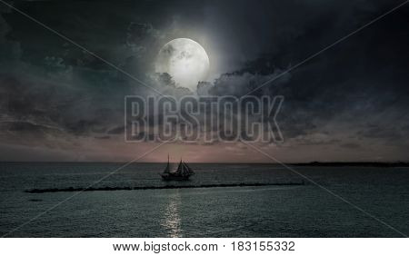 Yacht in the sea against the background of the big moon.