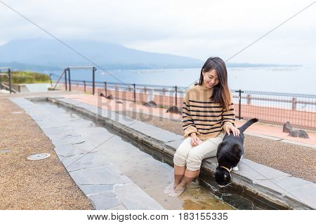 Woman enjoy her foot onsen with cat at outdoor