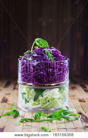 Detox salad diet concept. Fresh salad of autumn vegetables - purple and green cabbage and arugula - in a glass bowl on a bamboo background. Two-layered salad made of white and violet cabbage.
