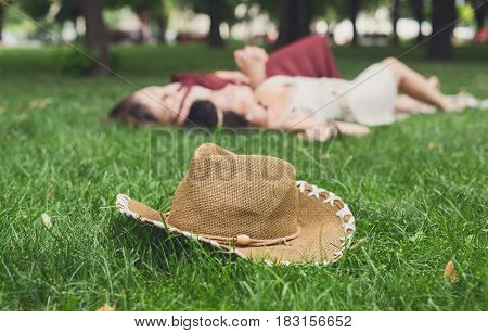 Girls unfocused relax in summer park, young hippie friends leisure. Focus on hat