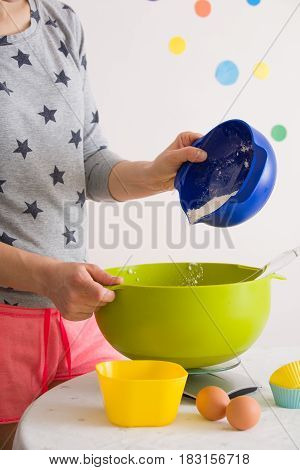 Woman making dough for muffins. Mixing flour sugar eggs and other ingredients from colorful bowls. Homemade food baking at home.