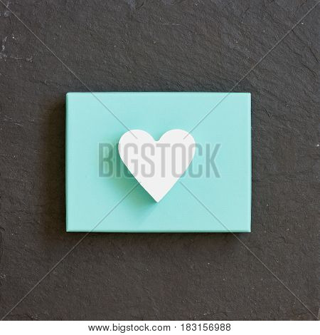 White heart on a turquoise color box on black background. Valentine's day. Present. Gift.