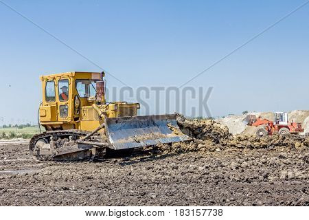View on heavy bulldozer while he moving leveling ground at construction site.