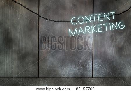 Neon text spelling content marketing against a wall