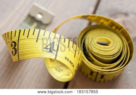 Close up of a measuring tape on a wooden background
