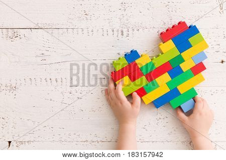 Top view on child's hands playing with bright heart made of colorful plastic bricks on old wooden table. Creative building out of bright constructor bricks. Early learning. Developing toys