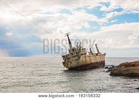 Abandoned broken ship-wreck beached on rocky sea shore
