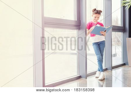 Full Length View Of Smiling Little Girl Standing Near Window And Reading Book