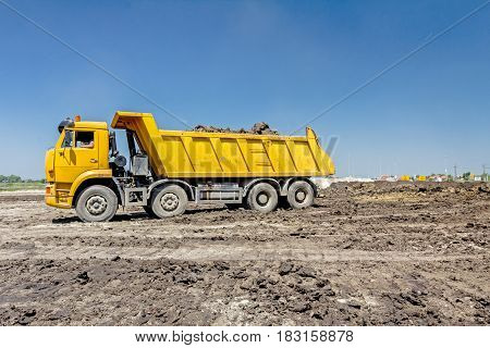Big hydraulic dump truck is moving into reverse prepare to unload cargo.