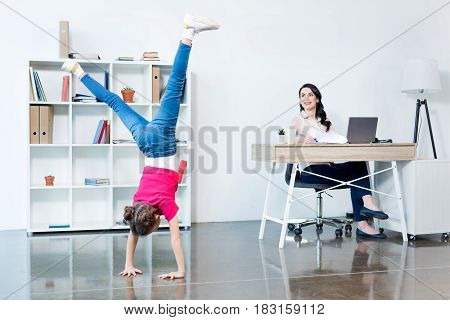 Smiling Businesswoman Using Laptop And Looking At Daughter Performing Handstand In Office