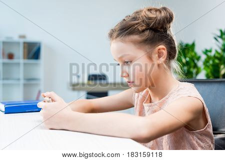Head And Shoulders View Of Adorable Little Girl Using Smartphone And Sitting At Table