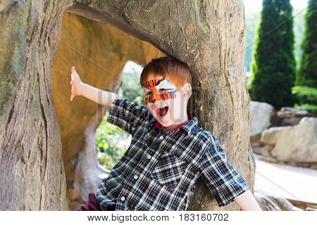 Small boy with funny face art painting. Male child sit in big old tree with tiger drawing on face. Children event, birthday party and creative entertainment.