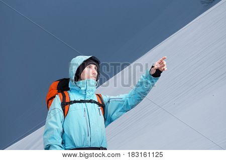 The mountaineer pointing on mountain slope, standing against a winter mountain landscape.
