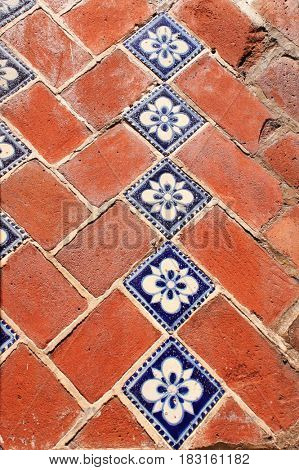 Old brick wall with ceramic inserts (talavera) - traditional brickwork in Puebla, Mexico