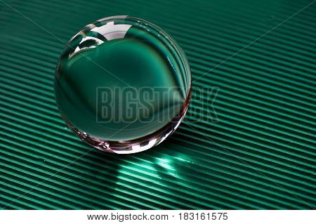Glass globe or drop of water on a background of green corrugated paper . Clean and Shine