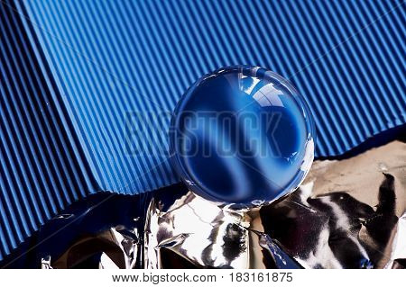 Glass globe or drop of water on a background of blue corrugated paper and foil . Clean and Shine