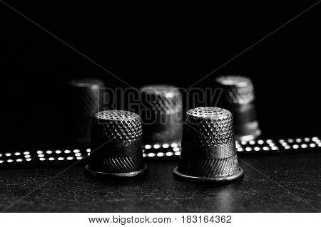 A few old thimbles on a black background. Brilliant bracelet. Monochrome.