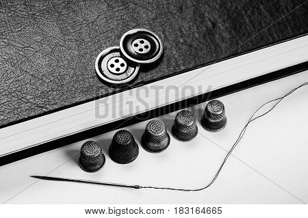 Gold Buttons on the book. Old Thimbles and a needle and thread on a background of book pages. Conceptual photography. Monochrome.