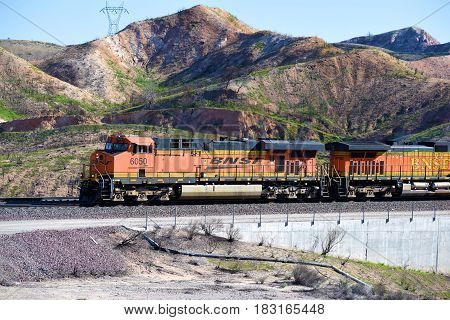 March 10, 2017 in Cajon, CA:  BNSF Freight Train riding southbound towards Los Angeles transporting commerce to LA and beyond taken in Cajon, CA where people can watch trains up close in a desert landscape
