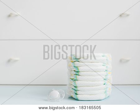 A stack of diapers against a white wardrobe. horizontally