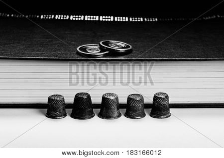 Thimbles are arranged in a row on the background pages of the book. The buttons on the book. Conceptual photography. Monochrome.