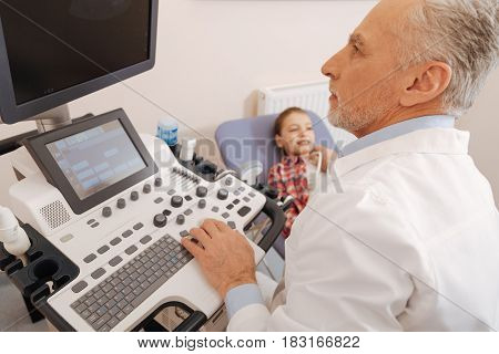 Your health under my control . Attentive senior experienced specialist working in the hospital and using ultrasound linear probe while providing thyroid gland scanning