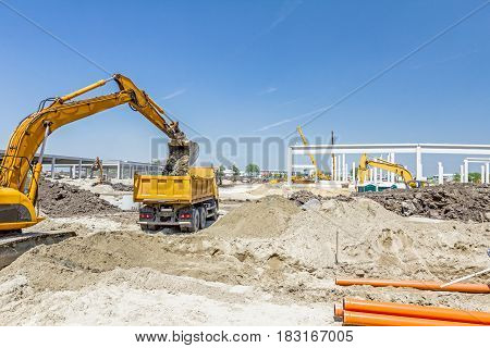 Big excavator is filling a dump truck with soil at construction site project in progress.