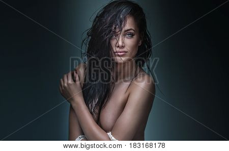 Sexy brunette woman posing naked with wet hair.