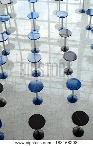 Abstract composition with many round eating tables staying in empty cafe hall vertical top view