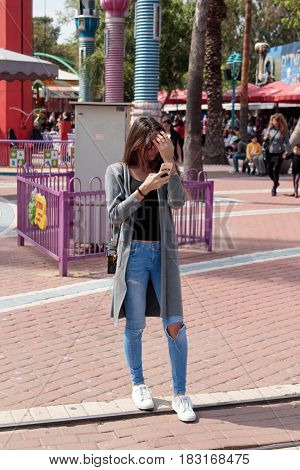 Tel Aviv Israel April 16 2016 : Young girl stands in a city's attractions park and looks in her cell phone in Tel Aviv Israel