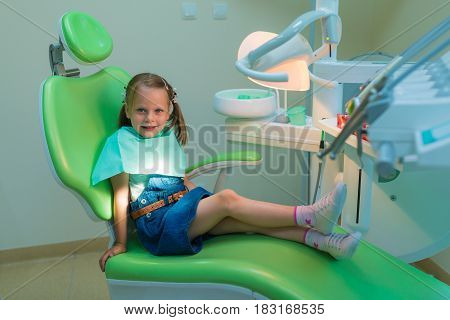 Healthy teeth patient girl waiting in dental chair in dentist office - dental caries prevention