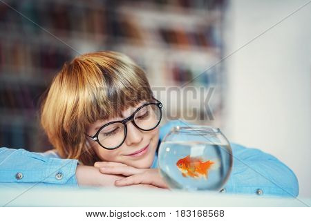 Little boy with goldfishin library