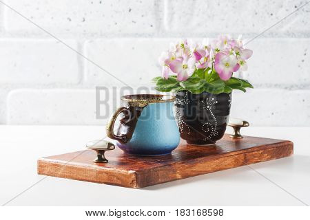 Cup Of Black Coffee With Croissant, Pink And White African Violet On White Table.