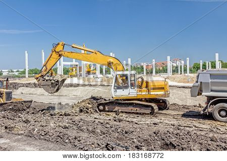 Big excavator is excavating soil at construction site project in progress.