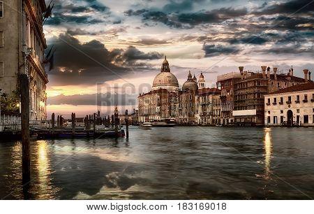 Dramatic sky over Grand Canal and Basilica di Santa Maria della Salute in Venice at sunset, Italy