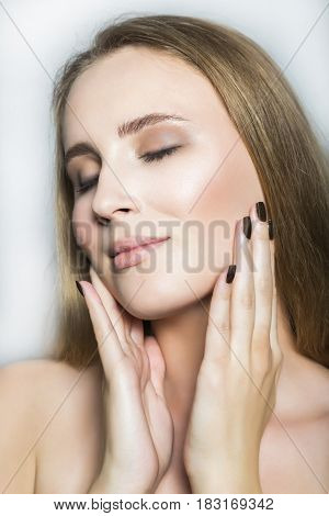 Portrait of young blonde beautiful girl with nude make up, with hands stroking her face with closed eyes on white background