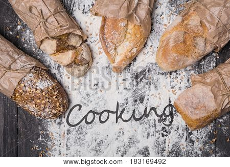 Baking and cooking concept background. Lots of different bread sorts, wrapped in craft paper top view with text on copy space on wooden table, sprinkled with flour. Soft toning