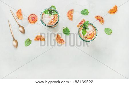 Blood orange fresh summer lemonade with ice and mint in glasses, light grey marble background, top view, copy space