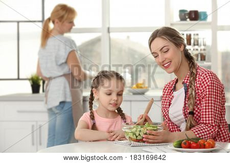 Young woman with her daughter in kitchen