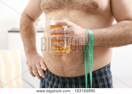 Man with big belly holding glass of beer and measuring tape at home