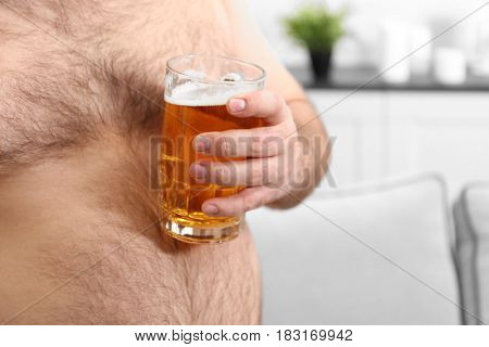 Man holding glass of beer on his big belly at home, closeup